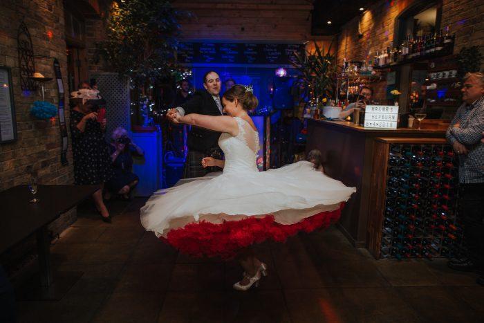 bride dancing in polka dot alternative wedding dress