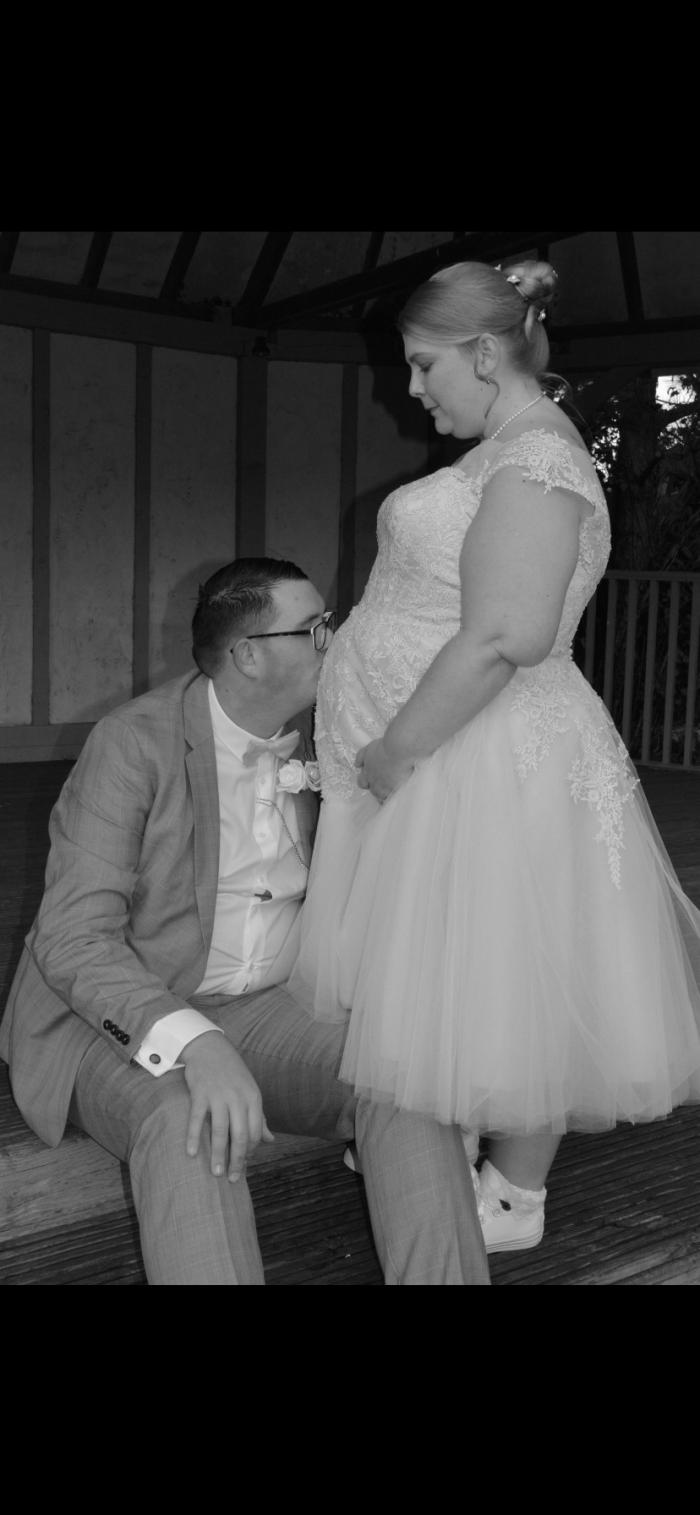 pregnant bride wearing a blush pink short wedding dress