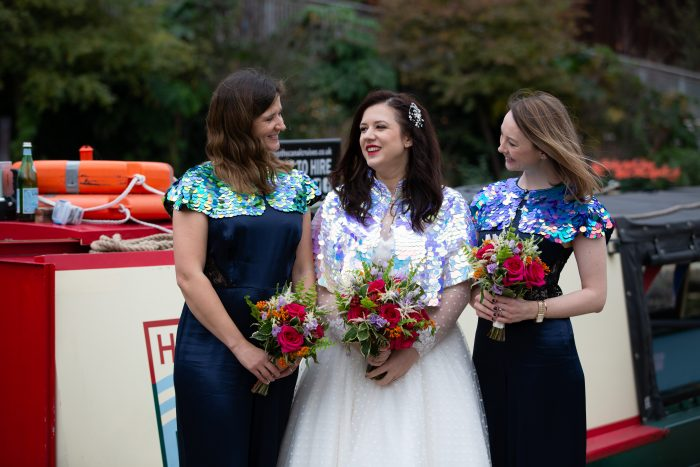 Bride and bridesmaids - bride wearing tea length wedding dress from Cutting Edge Brides