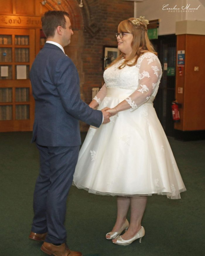 Bride and groom getting married, Bride wearing a tea length wedding dress