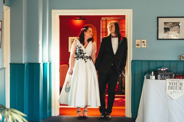 Bride and groom in a door way. Gorgeous bride wearing ivory satin wedding dress with black lace applique from Cutting Edge Brides