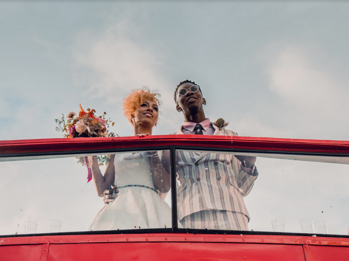 Real couple Paige and Benjamin - Bride wearing a short vintage style wedding dress and they are on a London Bus